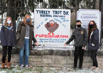 Cazenovia High School Class of 2023 leaders (left to right, Faith Wheeler, Maren Smith, Russell LaFever and Erin Kuhn) show off the sign for the 2020 Turkey Trot Virtual 5K Run/Walk. Local residents can sign up or donate to the event at runsignup.com. (Submitted)
