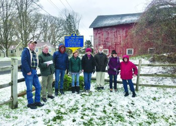 The Erieville-Nelson Heritage Society (ENHS) was recently awarded a New York State historic marker recognizing the location of Nelson's first town meeting, held April 7, 1807 on the Rufus Weaver Farm. On May 1, ENHS hosted a sign dedication ceremony at the intersection of Erieville and Old State Roads. Pictured left to right: Jim Georges, Kevin Davies, Fay Lyon, Laine Gilmore, Denise Earl, Tom Graves, Libbie Graves Holmes, and Miriam Barrows.  (Kate Hill)