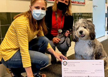Enders Road Home and School Association President Sarah Pinsky (left) and Principal Deborah Capri are pictured with the school's therapy dog, Bowie before presenting a $1,200 check to Helping Hounds Dog Rescue.