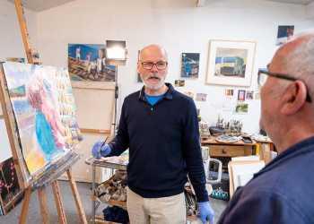 an older white man displays artwork