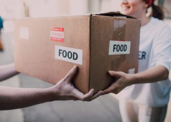 a volunteer hands a cardboard box of food to someone