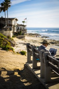 Man on a bench, seaside, beach house nearby