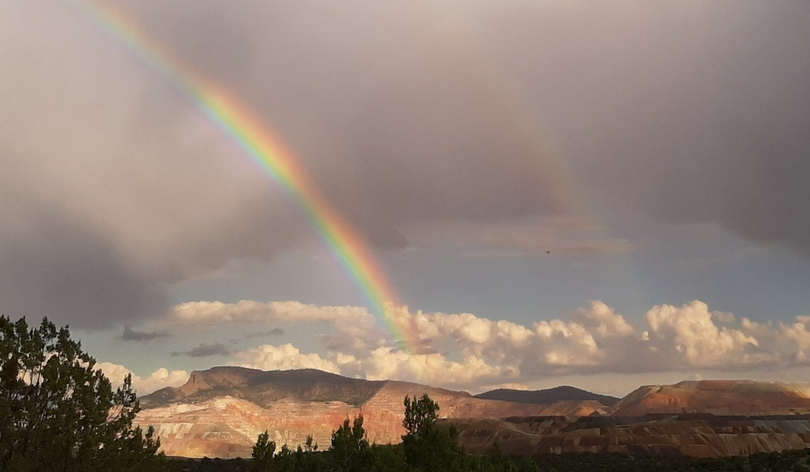 After a rain, a double rainbow in the eastern sky above hills