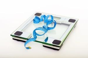 a home bathroom scale with a measuring tape atop it