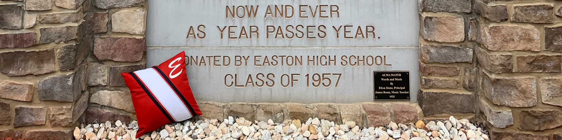 Uniform pillow resting in front of the Easton alma mater sign
