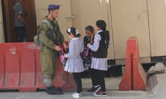 Soldiers check the bags of these girls in Hebron on their way to Cordoba school. Photo EAPPI/R. Kolehmainen