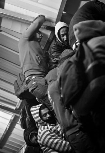 01.02.16. CP300. Men scramble over the entrance lane bars of CP300. Photo EAPPI/P. Morgan