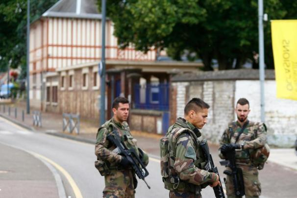 French soldiers stand guard at the scene of an attack that left a priest dead in Saint Etienne du Rouvray, Normandy, France on Tuesday. Photo Credit: US News