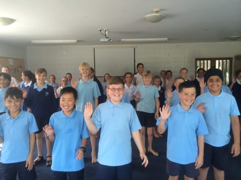Students playing traditional Maori game: Maui, Matau. The students follow the teacher's shouts of Maui (left) or Matau (right) and have to jump a quarter turn either left or right, if they don't turn or go the wrong way they sit down.