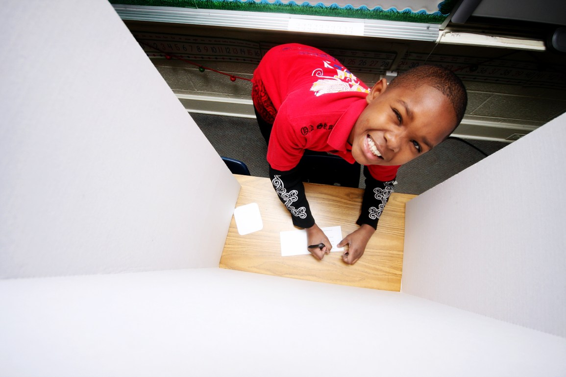 A child voting in a voting booth