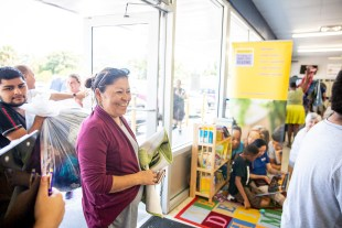 A woman carrying rugs to be washed into a laundromat smiles and laughs with a reading corner for children behind her.