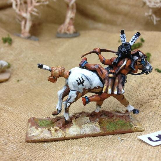 Sioux brave clinging to ponies side shooting bow,