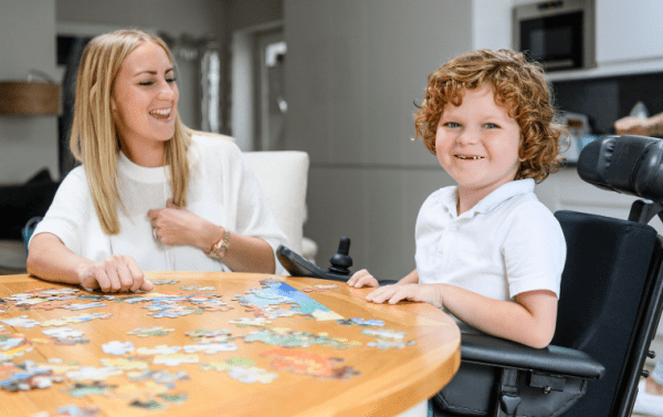 child in wheelchair doing a jigsaw with his mum at the table. EYFS physical and mathematical deevelopment minor fine motor skills childrens subscription box
