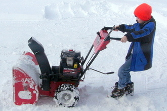 boy pulling snowblower