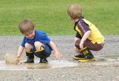 two boys playing in puddle