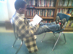 boy sitting on chair in library, reading a book
