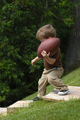 toddler boy walking holding football