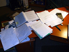 large pile of papers and books on desk