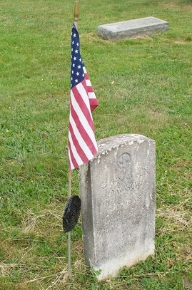 flag next to antique headstone in cemetery