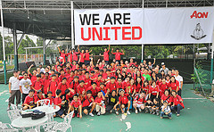 sports team posing together under sign that says We Are United