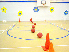 gymnasium with balls and cones set up in obstacle course