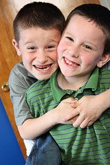 two boys hugging and smiling at camera