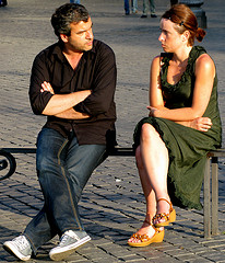 man and woman sitting on bench looking angry