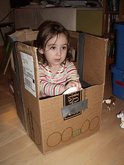 small girl playing in cardboard box