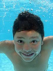 boy grinning at camera underwater