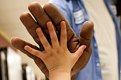 large man's hand giving high five to small child's hand