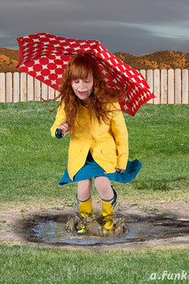 girl in raincoat with umbrella stomping in puddle