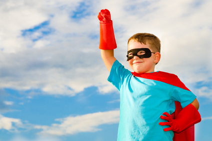 young boy in super hero costume striking heroic pose