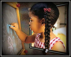 girl drawing picture on chalkboard