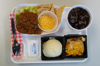school lunch tray with taco meat, chips, cheese, potatoes, beans, and corn