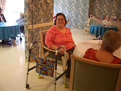 woman with walker in community room of nursing home