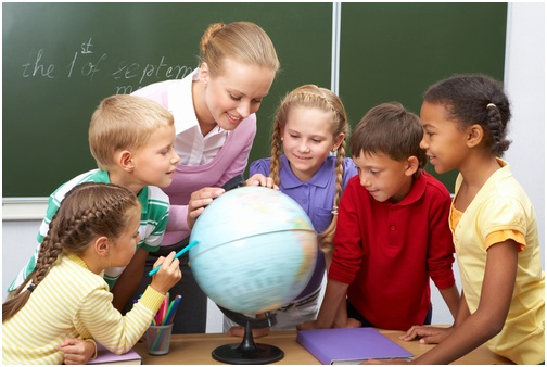 teacher and students looking at globe