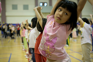little girl stretching in front of class