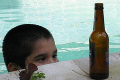 boy in pool looking longingly at beer bottle