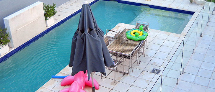 sun unbrella and table next to swimming pool