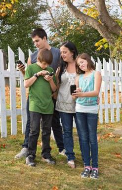 parents hugging two children who are holding cell phones