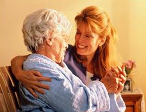 young woman smiling and hugging elderly woman