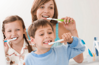 mom with son and daughter, all brushing teeth
