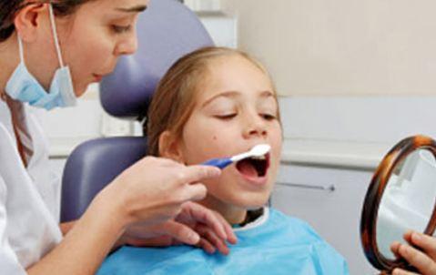 girl brushing teeth at dentist