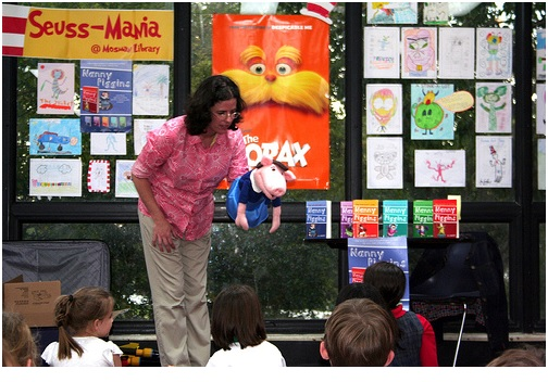 librarian telling story to children, holding puppet