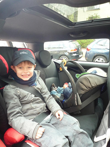 smiling boy in back seat of car next to infant