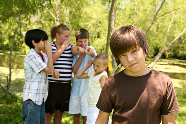 teen boy being teased by group of children behind him.