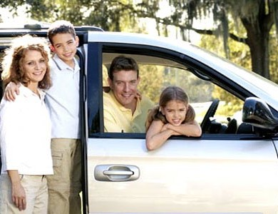 parents, son, and daughter in front of family car