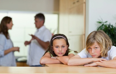 children looking sad while parents argue in background