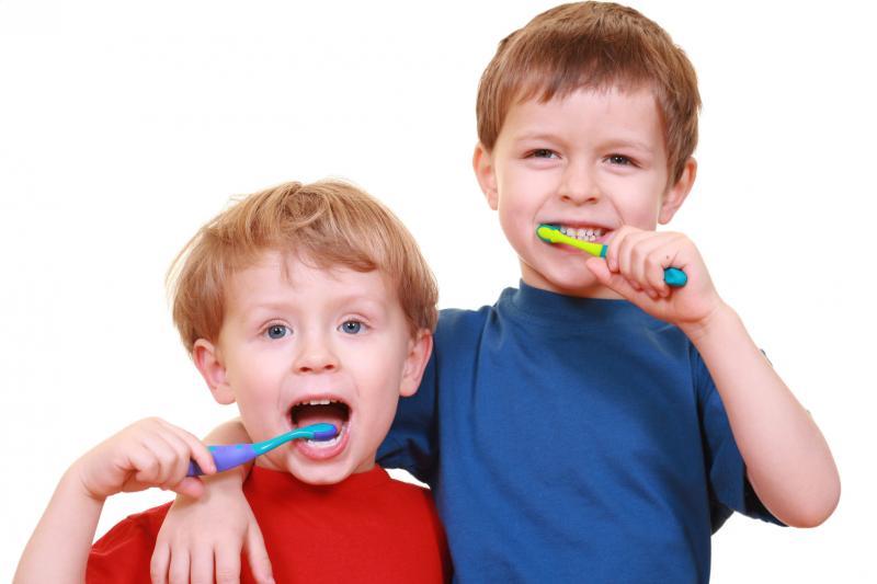 2 boys cheerfully brushing their teeth