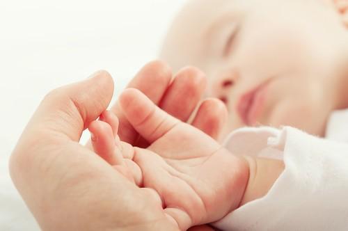 parent's hand holding hand of sleeping baby